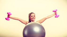 Girl warming up with ball and dumb bell weights. Exercise sport fitness health concept. Fit girl exercising. Attractive female warming up with ball and dumb Stock Images