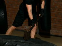 Exercise sports men with a large wheel and a sledgehammer, against a brick wall background. Exercise sports man with a large wheel and a sledgehammer, against a Stock Image