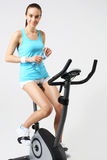 Exercise on a stationary bike, a woman in a fitness club Royalty Free Stock Images