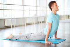 Exercise for stretching. Portrait of young man doing stretching exercise in gym Royalty Free Stock Image