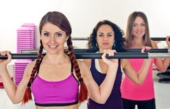 Exercise for three. Young women shows exercise in fitness club Stock Images