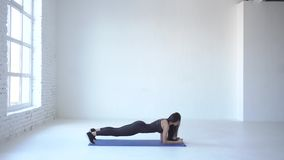 The exercise of up down plank is performed by young athletic sportswoman on the yoga mat in white studio. 4k. The exercise of up down plank is performed by stock video