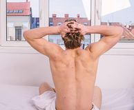 Exercise daily. Vigorous exercise is best but even light exercise better than no activity. Man muscular back stretching. Hands while sit bed rear view. Get stock images