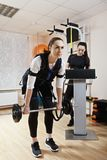Exercise with weight. Caucasian women makes exercise with weight in gym. Female trainer standing aside manages electric muscle stimulation purposed to increase Royalty Free Stock Photos
