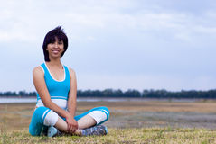 Exercise woman. Exercise young woman relaxed seated outside Stock Image