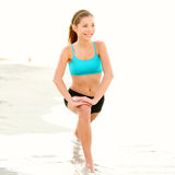 Exercise woman stretching on beach Royalty Free Stock Images