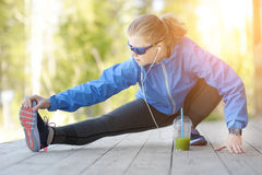 Exercise woman stretching hamstring leg muscles duing outdoor ru Stock Images