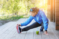 Exercise woman stretching hamstring leg muscles duing outdoor ru Royalty Free Stock Images