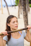 Exercise woman training arms on pull-up bar. Doing chin-ups. Asian mixed race chinese caucasian female athlete working out on horizontal bars outside on beach stock photography