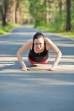 Exercise woman training doing push-ups outside Royalty Free Stock Photo