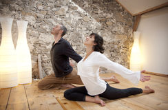 Exercise and Yoga. Young couple using yoga to exercise Royalty Free Stock Images