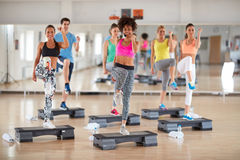 Exercisers with female instructor on group training Stock Photo