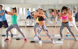 Exercisers grupperar att göra övningar med resistent gummi i fitnes royaltyfri bild