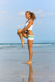 Exercises. Sports girl doing exercises on the beach Royalty Free Stock Photography