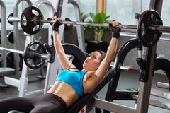 Exercises with barbell. Young woman lying on bench and doing exercises with barbell stock photos