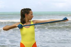 Exercises with elastic band. Woman in yellow leotard doing exercises with elastic band Stock Photos