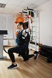 Exercises with electric stimulation. Caucasian women makes sit-ups with weights in gym. Female trainer standing behind assists.  Electric muscle stimulation is Royalty Free Stock Photos