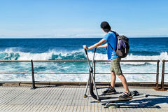 Exercises everyday outdoor. Teenager working exercises on equipment and enjoying ocean. royalty free stock photography