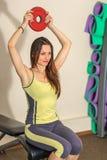 exercises fitness physical Το νέο όμορφο λευκό κορίτσι σε ένα κίτρινο και γκρίζο αθλητικό κοστούμι εκπαιδεύει με έναν βλαστό από  στοκ φωτογραφία