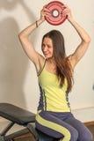 exercises fitness physical Το νέο όμορφο λευκό κορίτσι σε ένα κίτρινο και γκρίζο αθλητικό κοστούμι εκπαιδεύει με έναν βλαστό από  Στοκ φωτογραφία με δικαίωμα ελεύθερης χρήσης