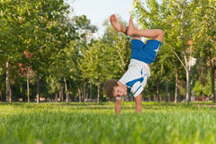 Exercises on the grass in the park. A boy carries athletic exercises on the grass in the park stock images