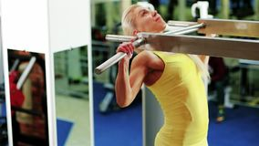 Exercises on the horizontal bar, the girl performs a pulling up exercise, athletic woman at the gym, playing sports as a stock video footage