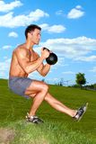 Exercises with kettlebell in sunny weather Stock Photos