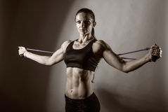 Exercises with a resistance of. Sportswoman exercising with a resistance band. Black and white photo Stock Photo