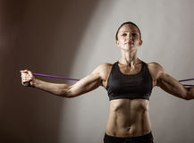 Exercises with a resistance of. Sportswoman exercising with a resistance band on grey  background Stock Photos