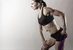 Exercises with a resistance of. Sportswoman exercising with a resistance band on grey  background Royalty Free Stock Photo