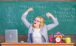Exercises to maintain vivacity. Teacher woman sit table classroom chalkboard background. Work far beyond actual school. Day. Stretch and do exercises to stock image