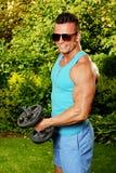 Exercisess молодого человека с dumbells Стоковое Изображение