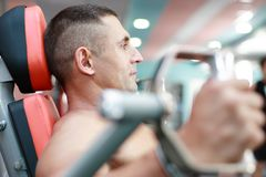 Exercising. The young athlete is engaged on the sports exercise machine Royalty Free Stock Images