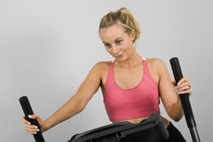 Exercising. Caucasian woman in early 20s exercising on a cardiovascular machine Royalty Free Stock Image