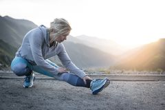 Exercising adult woman outdoors. Sports and recreation. Exercising adult woman outdoors. Sports and recreation stock image
