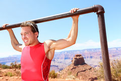 Exercising athlete doing pull ups in nature. Exercising Fitness athlete man training pull ups in amazing nature landscape of Grand Canyon. Strength training fit Stock Image