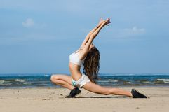 Exercising on the beach. Young woman making exercise on the beach Stock Images