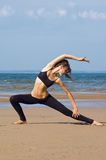 Exercising on the beach. Young woman making exercise on the beach Royalty Free Stock Image