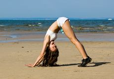 Exercising on the beach. Young woman making exercise on the beach Royalty Free Stock Photo