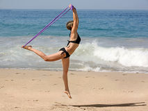 Exercising on the beach. Woman Exercising on the beach with a rubber band Royalty Free Stock Photos