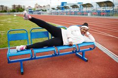 Exercising on bench. Young active woman in white sweatshirt, leggins and cross-shoes lying on bench and raising leg Royalty Free Stock Photography
