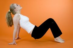 Exercising blond. Young and beautiful blond girl wearing sport clothes and exercising; posing in a studio; isolated on orange background Royalty Free Stock Photos