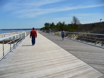 Exercising on the Boardwalk. People walking and running on the boardwalk for their health stock photo