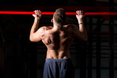 Exercising on chin-up bar. Young attractive caucasian crossfit sportsman working out in gym, exercising on chin-up bar, doing pull-ups for arms and back muscles Stock Image