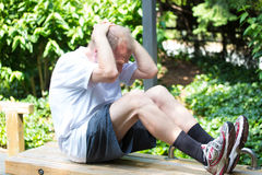 Exercising. Closeup portrait, healthy elderly man doing sit-ups on bench outside,  green trees background Stock Photo