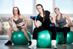 Exercising with dumbbells on balls Stock Photo
