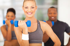 Exercising with dumbbells. Cheerful young women and friends exercising with dumbbells Stock Image