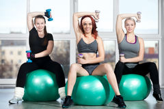 Exercising with dumbbells on fitballs Royalty Free Stock Image
