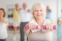 Exercising with dumbbells. Senior women exercising with pink dumbbells during classes Royalty Free Stock Photo