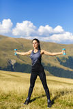 Exercising fitness woman doing exercises in nature. Girl doing m Stock Photos